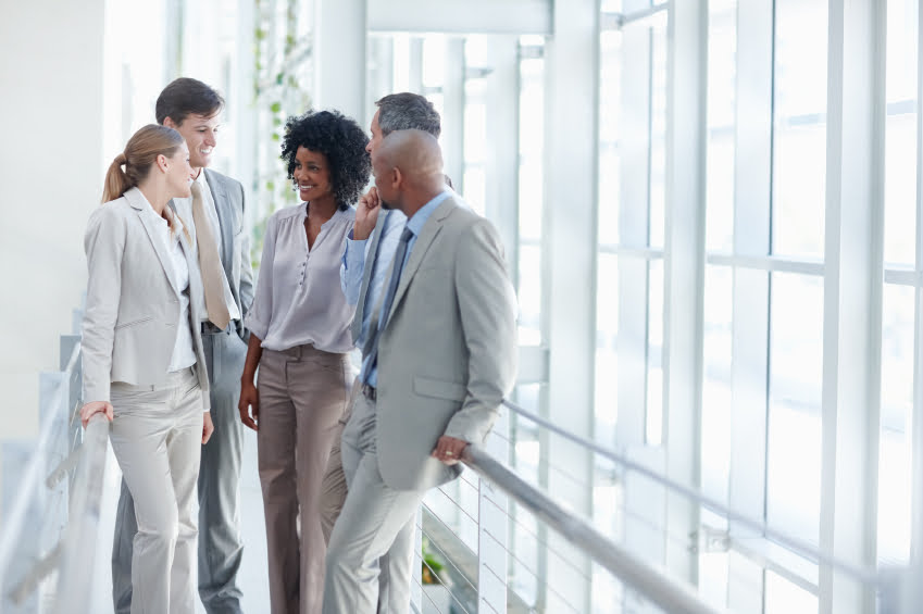 Business colleagues stop to have a conversation in their workplace - Copyspace